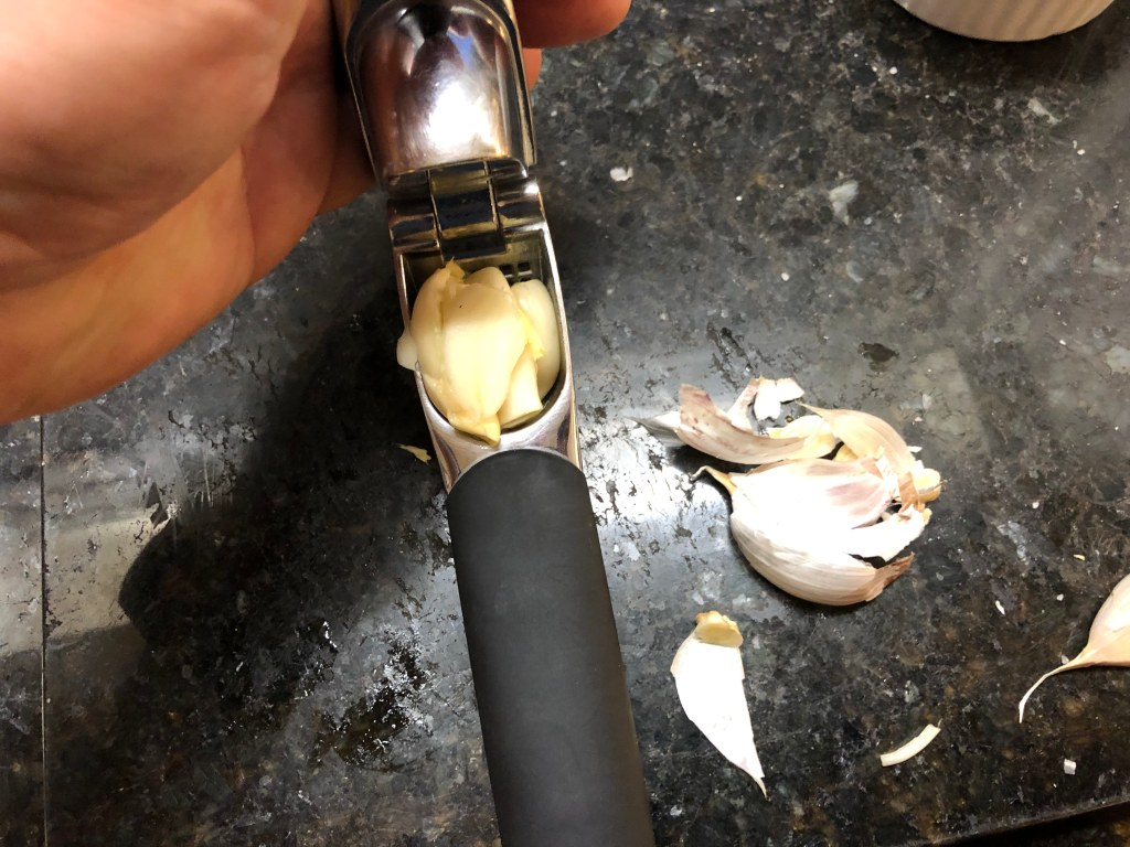 If you're using your garlic press fill the chamber with as many cloves as will fill it (some cooks leave the paper on the clove when using a press... you can simply pull it out of the chamber after pressing the clove. I just find this messy so I pull the paper off first