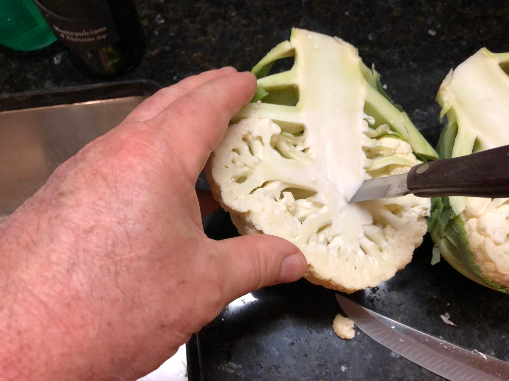 To prepare the cauliflower, start by slicing it in half. Cut on the diagonal from each side of the top of the root the length of the head