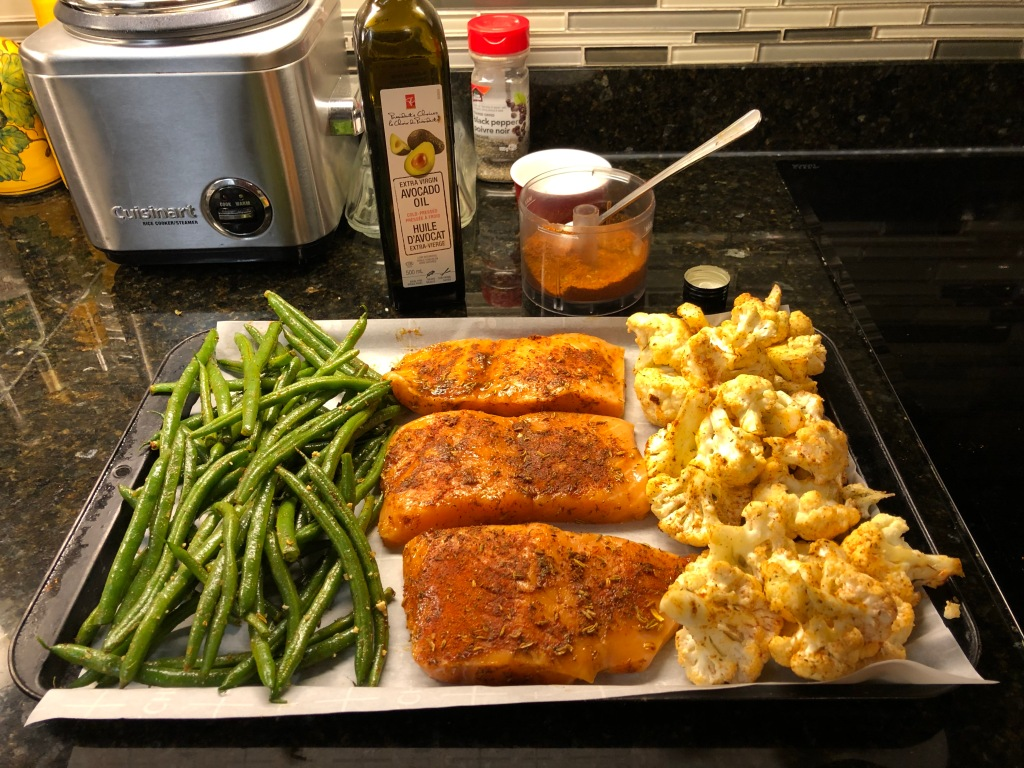 Preheat oven to 450. Line a shallow baking sheet with parchment paper. Arrange the vegetables and salmon as pictured. (To satisfy a picky eater at my house I actually toss the beans and cauliflower in oil independently.)