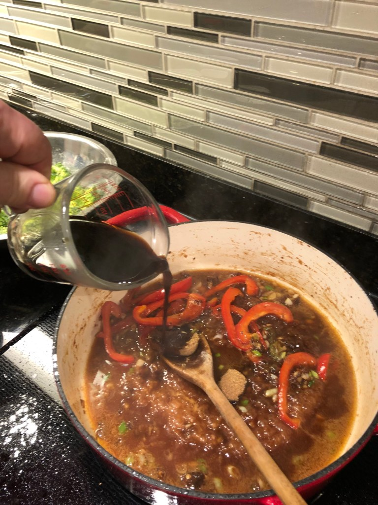 Once the beef has been browned, remove from the pan and set it aside.  Add another tablespoon of oil and stir fry garlic for 30 seconds until fragrant. Add peppers and green onions for 2-3 minutes.  Add beef broth, brown sugar and sriracha and bring to a boil