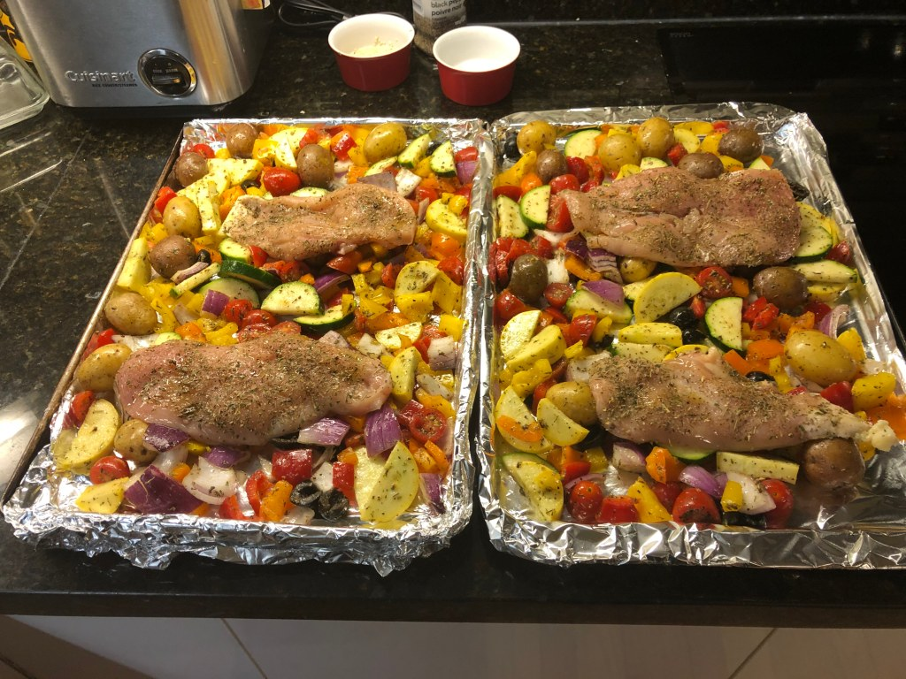 Prepare the sheet pans with aluminum foil, spray with olive oil and cover those with the veggies and chicken