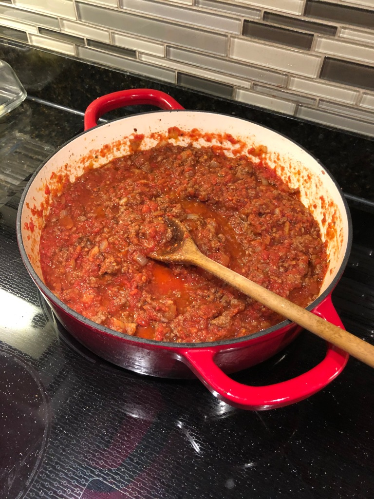 Return saucepan over medium heat and add tomato paste and oregano.  Cook for 2 minutes more, until slightly darkened. Add crushed tomatoes and bring sauce to a simmer