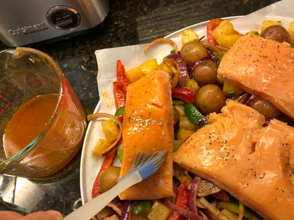 Top veggies with salmon fillets and brush with any remaining honey spice mixture