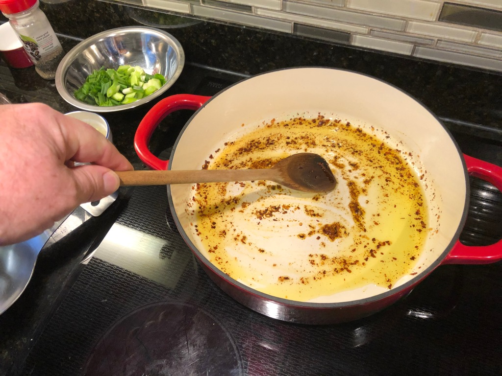 Heat oil in a large deep skillet over medium-high heat.  Add red pepper flakes to oil, stir a few times