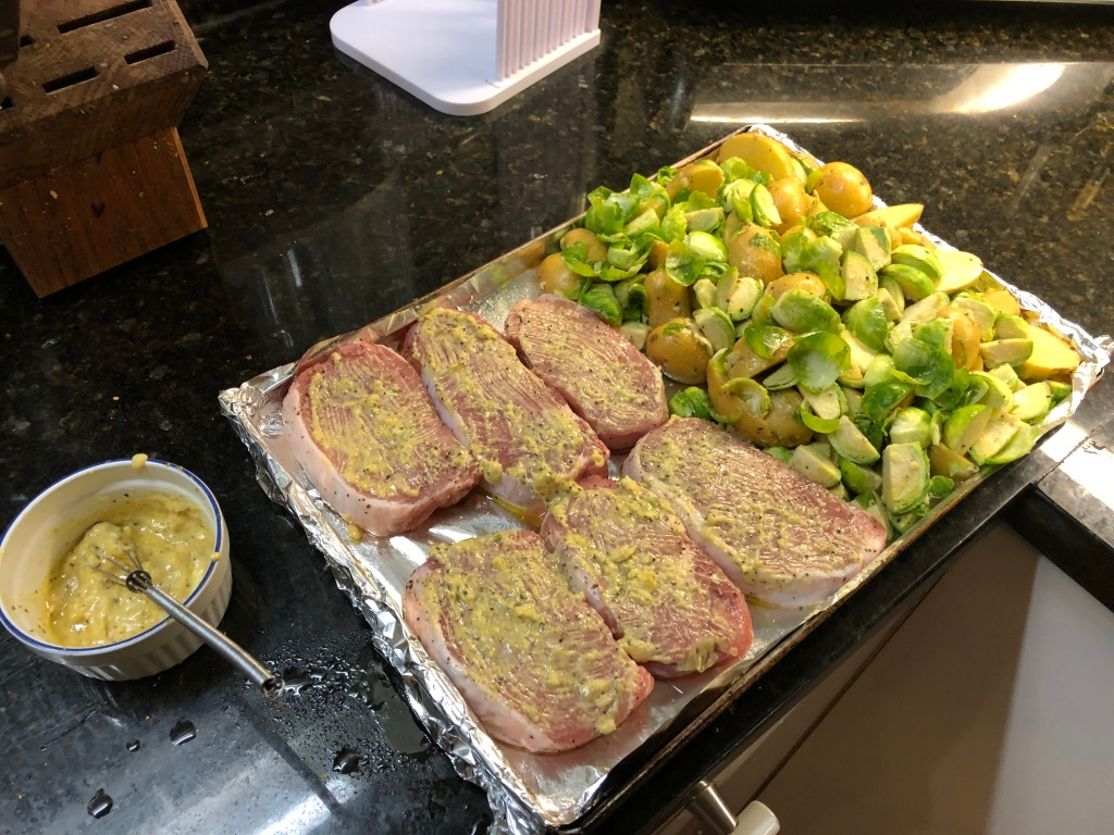 After tossing the veggies in the remaining mustard sauce, place the chops and veggies onto a prepared baking sheet