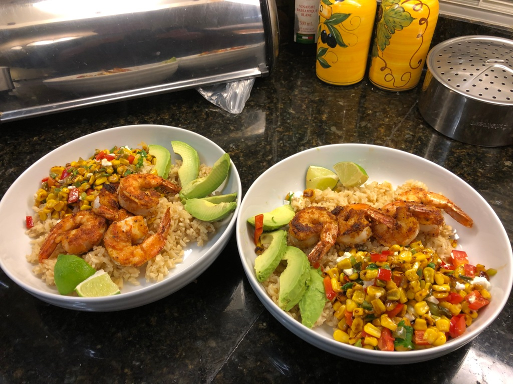 Build bowls: divide rice between 4 bowls. Top with shrimp, corn salad, and 1/4 avocado each. Garnish with cilantro, squeeze with lime and serve.