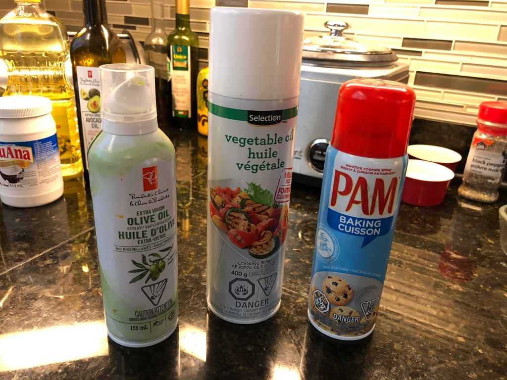 Most grocery stores offer cooking oils in handy spray form.  I use these generally only in special applications like when I'm baking or want to use only a little oil in a recipe