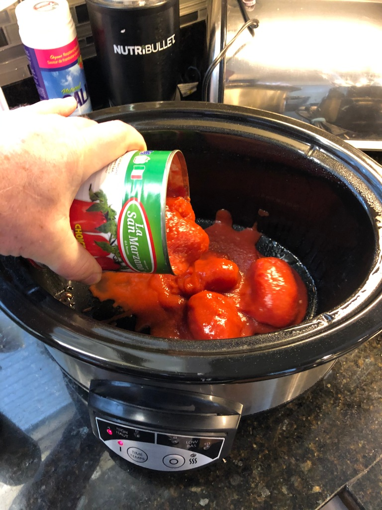Add whole tomatoes to preheated slowcooker