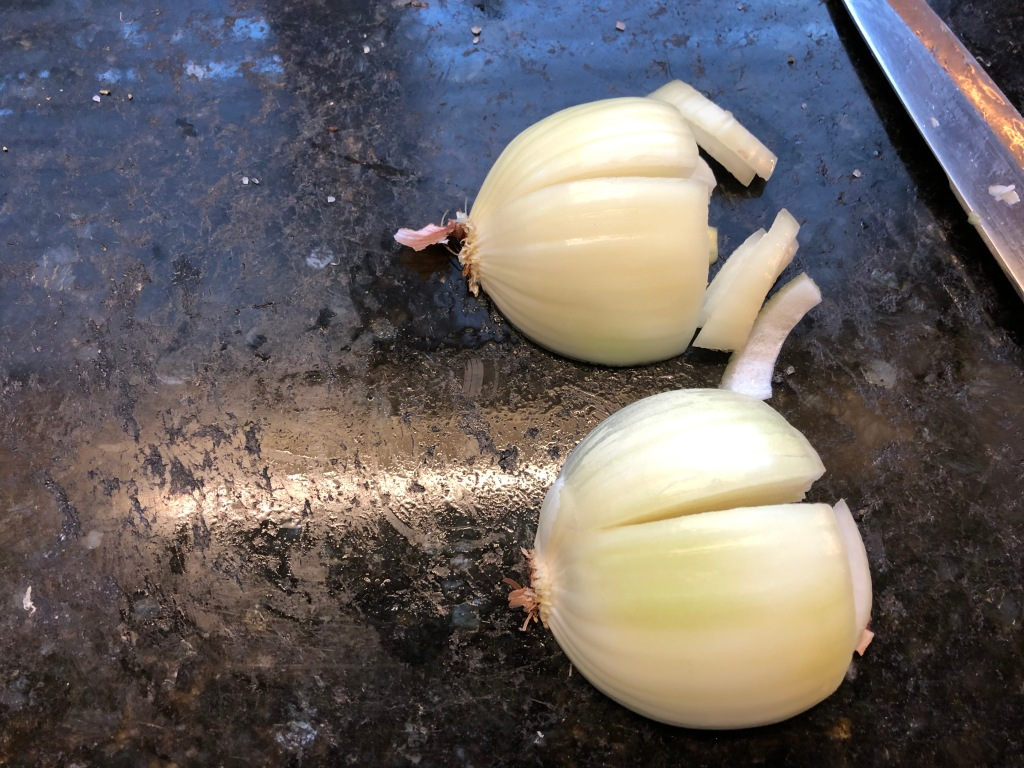 Cut the onion in half through the root then slice each half in half again to produce what I call half-rings