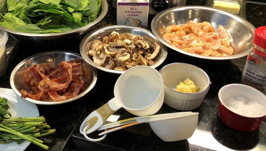 Thinly slice chicken breasts. Mince garlic cloves. Slice mushrooms. Chop bacon slices and reserve spinach for later.