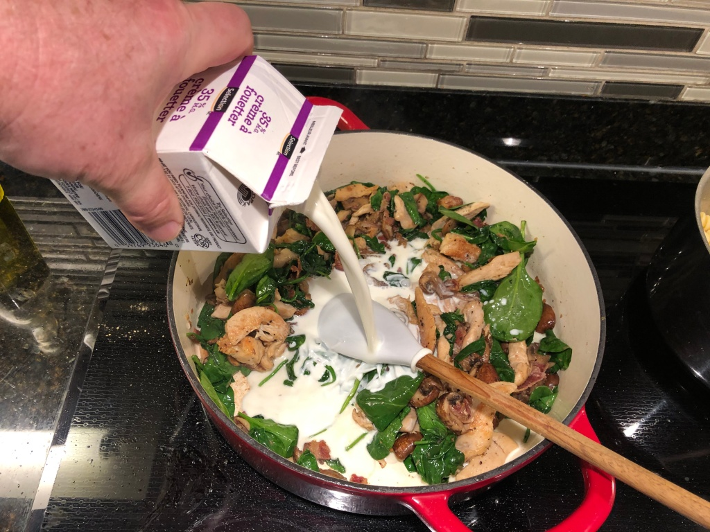 Once spinach has begun to wilt, add the cream or milk and mix thoroughly