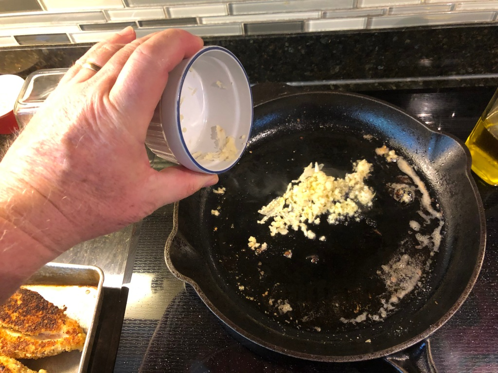 Once the chicken has been coated and browned, set it aside, add a little more oil to the skillet turn the heat down to medium and add the garlic