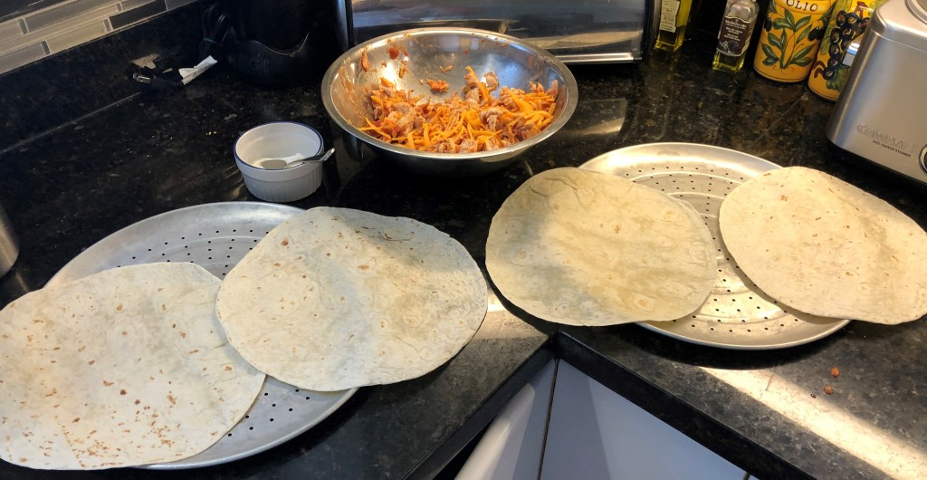 Spray two pizza pans with a little olive oil and lay out four flour tortillas.